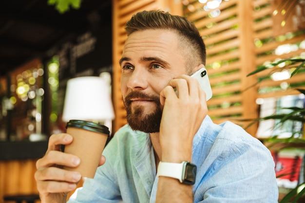 Bel giovane uomo barbuto felice che parla dal telefono cellulare che beve caffè.