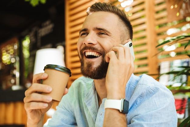 Bel giovane uomo barbuto felice che parla dal telefono cellulare.