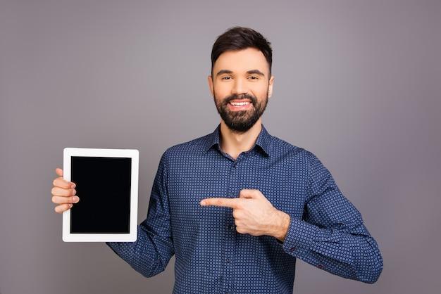 Handsome giovane uomo d'affari felice che punta sullo schermo del tablet