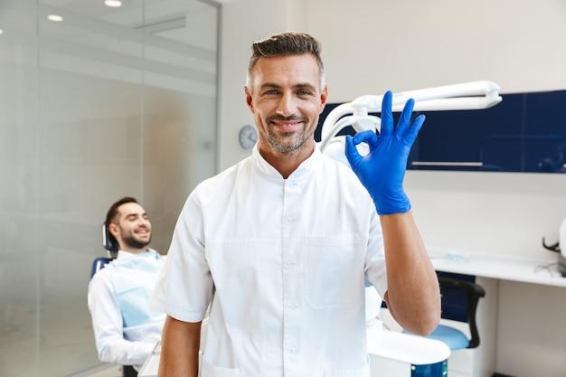 Bel giovane felice medico nel centro medico dentista che mostra il gesto giusto