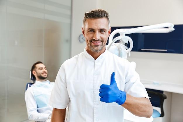 Bel giovane medico felice nel centro medico dentista che mostra i pollici in su