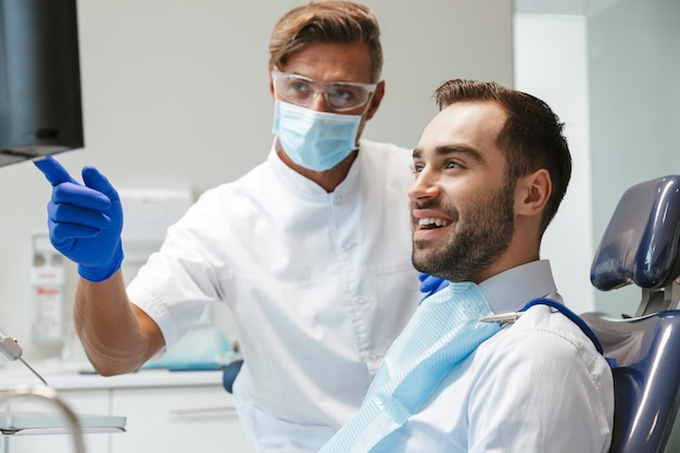 Bel giovane felice seduto nel centro medico dentista guardando la scansione a raggi x