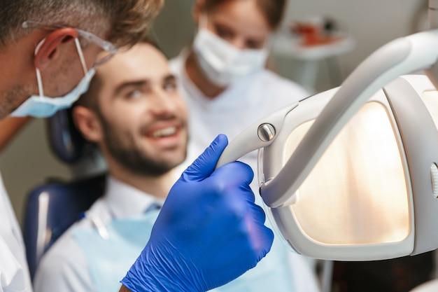 Bel giovane felice uomo seduto nel centro medico dentista