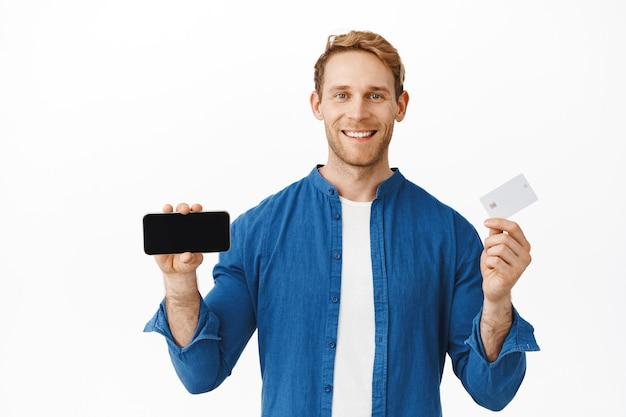 Bell'uomo in buona salute che mostra lo schermo orizzontale dello smartphone e la carta di credito, sorride felice mentre consiglia di scaricare l'app, visitare il negozio online, pagare con carta di credito, muro bianco