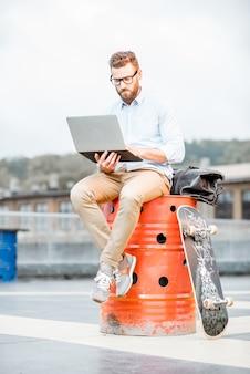Bello uomo d'affari hipster che lavora con il computer portatile nel parco giochi sul tetto dell'edificio industriale. concetto di stile di vita aziendale
