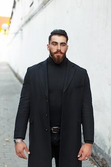 Uomo bello hipster con la barba in un cappotto nero sulla strada