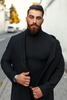 Uomo bello hipster con la barba in un cappotto alla moda nero in una giornata autunnale sulla strada
