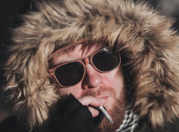 Uomo alla moda hipster bello che fuma fuori nel contesto urbano,