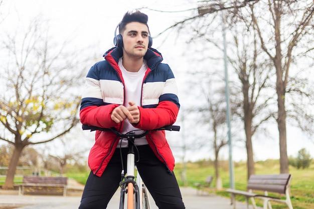 Giovane bello dei pantaloni a vita bassa che gode di un giro in bicicletta e che per mezzo di uno smartphone mentre ascoltando musica dalle cuffie