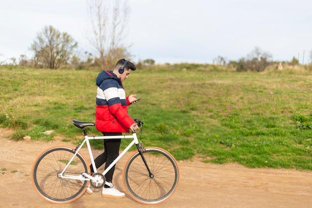 Giovane bello dei pantaloni a vita bassa che gode di un giro in bicicletta e che per mezzo di uno smartphone mentre camminando sul parco