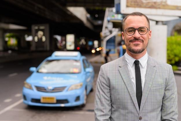Uomo d'affari barbuto calvo ispanico bello con gli occhiali alla stazione dei taxi della città