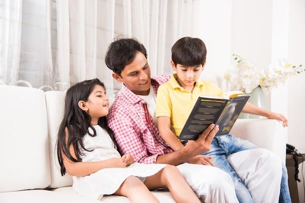 Bel padre indiano asiatico o bella madre che legge un libro per bambini seduti sul divano di casa at