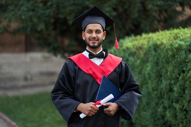 Bello laureato indiano in bagliore di laurea con diploma che guarda l'obbiettivo.