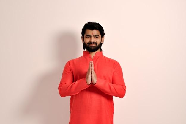 Bell'uomo indiano che indossa kurta sorridente facendo il gesto di namaste con le mani che guardano la telecamera