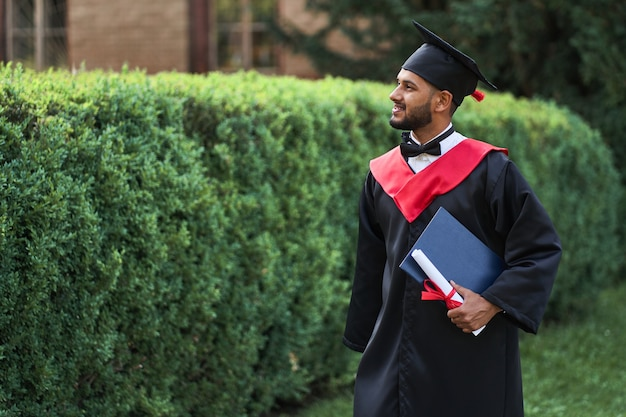 Bello studente indiano che celebra la laurea nel campus universitario con diploma in veste.