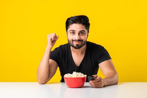 Bello uomo barbuto indin che mangia popcorn dalla ciotola rossa mentre è seduto a tavola su sfondo giallo