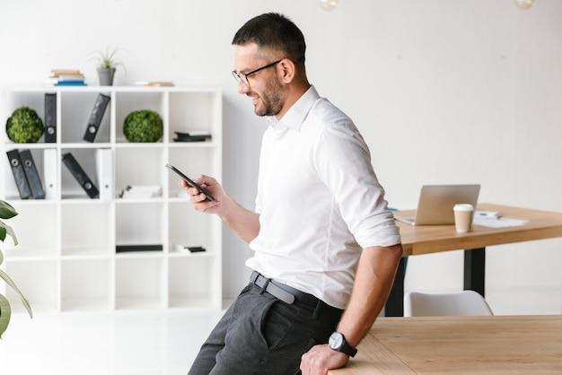 Bell'uomo gioioso che indossa una camicia bianca seduto sul tavolo in ufficio e utilizza lo smartphone per chat di lavoro