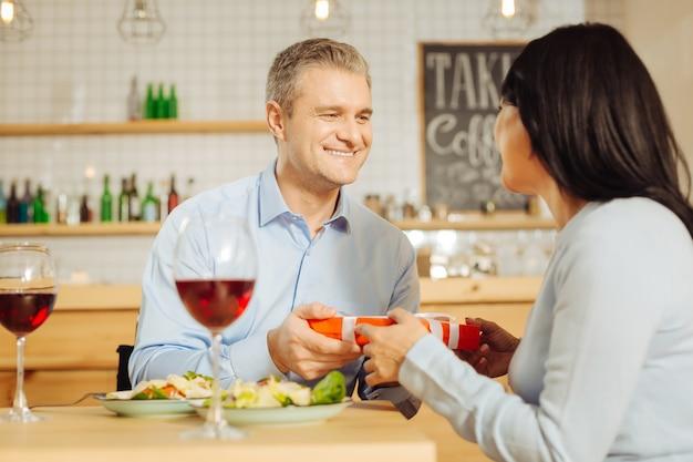 Bell'uomo gioioso ben costruito che sorride e dà un regalo alla sua attraente amata donna felice mentre si cena romantica