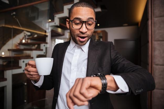 Bello tardo uomo africano in tuta con una tazza di caffè in mano guardando l'orologio da polso in hotel