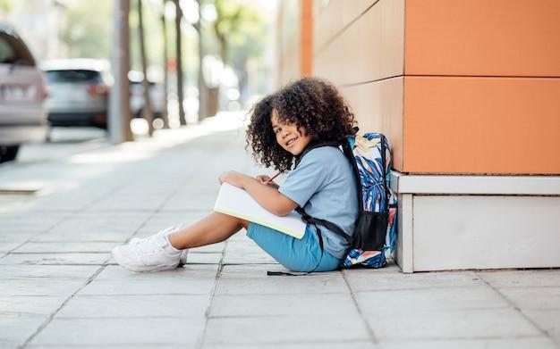 Bel ragazzino afro fa i compiti dopo la scuola, seduto per terra, in età prescolare