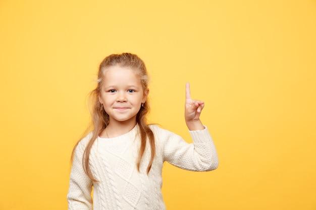 Bambina bella che indica qualcosa di isolato in studio giallo