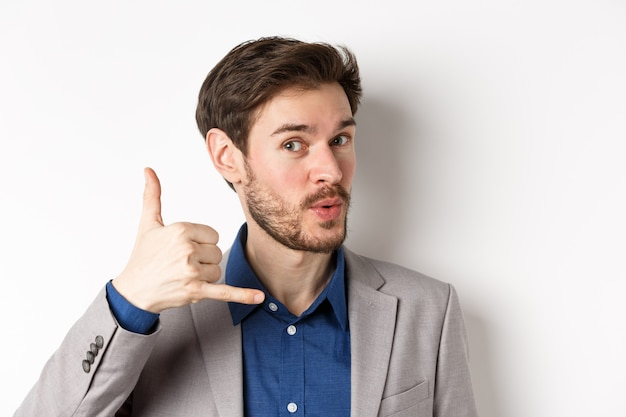 Bel ragazzo macho in vestito che mostra il segno del telefono vicino all'orecchio, flirtando e chiedendo di chiamarlo Foto Premium