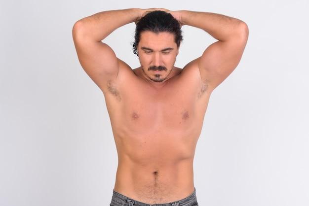 Bell'uomo macho con capelli ricci e baffi contro il muro bianco