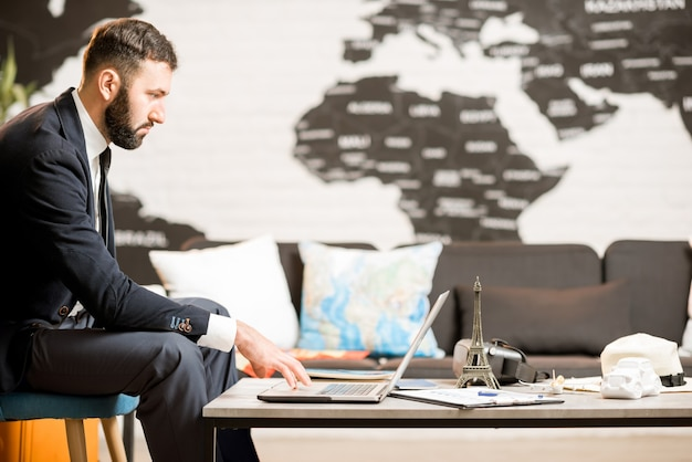 Bell'agente maschio che lavora con il computer portatile presso l'ufficio dell'agenzia di viaggi con mappa sullo sfondo