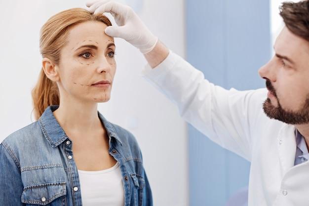 Bel chirurgo estetico maschio guardando il suo viso di pazienti ed esaminandolo mentre la preparava alla chirurgia estetica