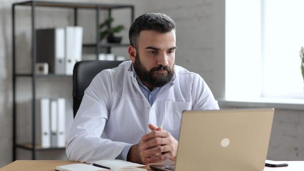 Il dottore maschio bello ha videochiamata, chat video, conferenza con i colleghi o paziente remoto online utilizzando la webcam sul laptop.