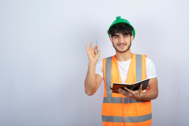 Assistente tecnico maschio bello in elmetto protettivo verde con il taccuino che sta sopra il muro bianco. foto di alta qualità