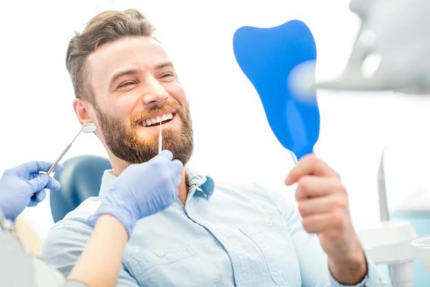 Bel paziente maschio che guarda il suo bel sorriso seduto nello studio dentistico