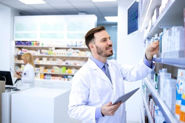 Farmacista maschio bello in camice bianco che lavora in farmacia o in farmacia e controlla i farmaci sul suo tablet.
