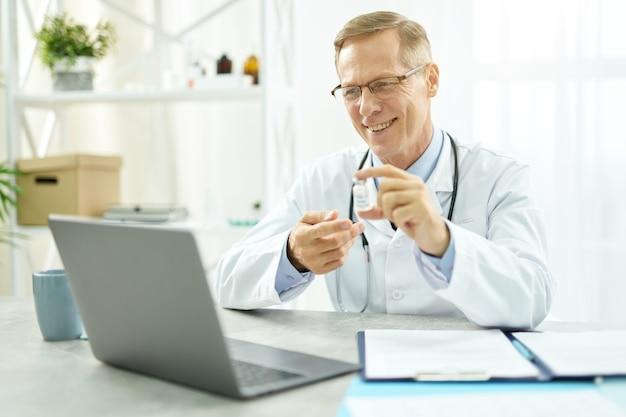 Bel medico maschio seduto al tavolo con il taccuino e sorridente mentre discute del vaccino covid-19 con il paziente durante la consultazione online