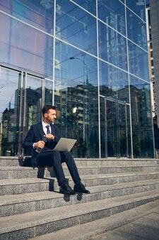 Bel maschio seduto sulle scale del centro affari e lavora online mentre apre una bottiglia d'acqua