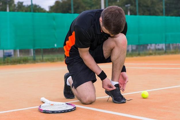 Giocatore di tennis maschio bello che lega i lacci delle scarpe che indossano una racchetta e una palla sinistra degli abiti sportivi su un campo in terra battuta all'aperto in estate o in primavera