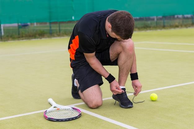 Bel giocatore di tennis maschio legare i lacci delle scarpe che indossa un abbigliamento sportivo sinistra racchetta e palla su un campo in erba verde all'aperto in estate o in primavera