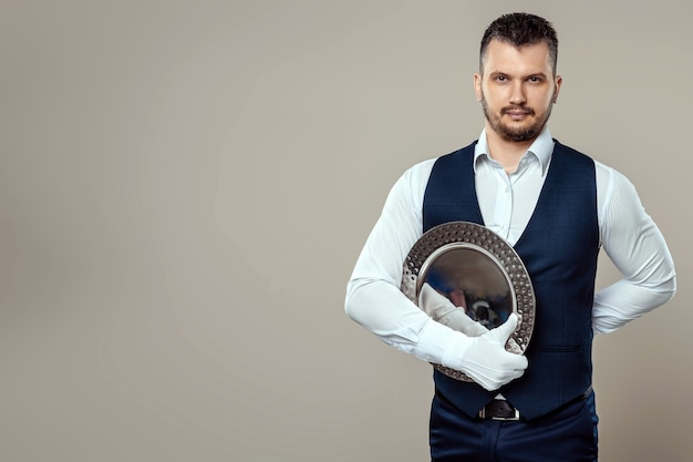 Bel cameriere maschio, camicia bianca, tiene un vassoio d'argento, mano dietro la schiena. concetto di camerieri che servono i clienti in un ristorante.