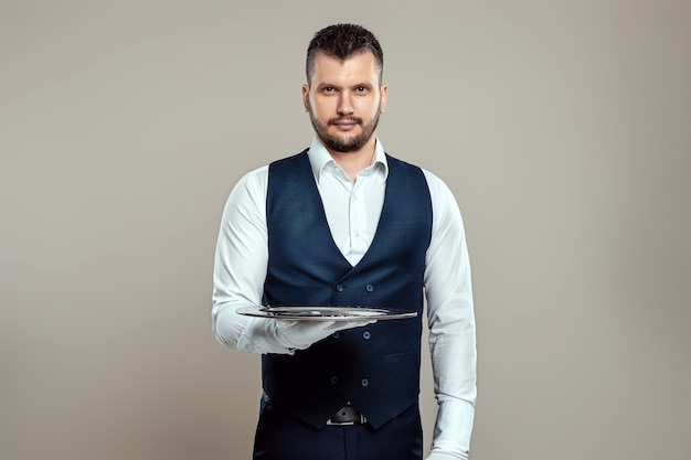 Il cameriere maschio bello, in una camicia bianca, tiene un vassoio d'argento sulle braccia tese. il concetto di personale di servizio che serve i clienti in un ristorante.