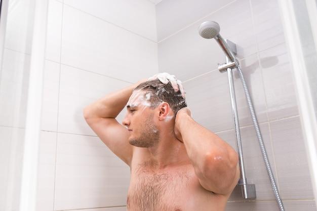 Bel maschio lavando i suoi capelli di schiuma gocciolante nella cabina doccia nel moderno bagno piastrellato