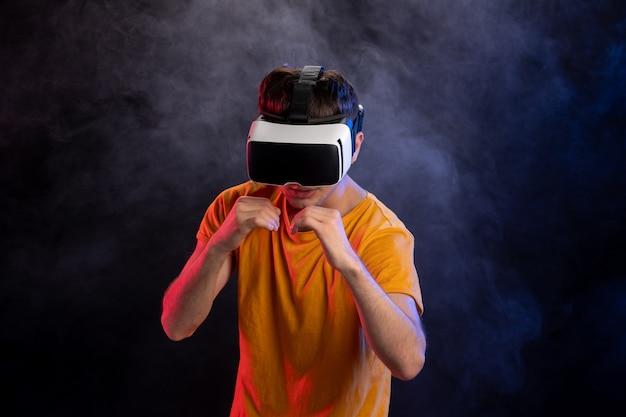 Bel maschio che indossa le cuffie da realtà virtuale sulla superficie scura