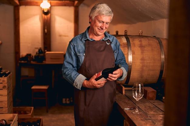 Bello enologo maschio in grembiule che guarda una bottiglia di bevanda alcolica e sorride mentre trascorre del tempo nella conservazione del vino