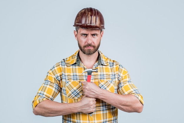 Assistente uomo bello nel casco di sicurezza della costruzione e camicia a scacchi in cantiere con martello, miglioramento.