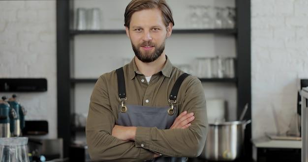 Barista uomo bello in piedi al bancone del bar, guardando la fotocamera e incrociando le mani. cameriere in posa nella caffetteria con attrezzature per bevande sullo sfondo.