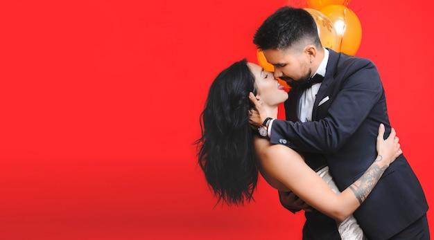 Bell'uomo e bella donna in abiti eleganti che abbracciano e si baciano stando vicino a palloncini carini su sfondo rosso vibrante
