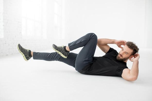 Bell'uomo con l'abbigliamento sportivo nero che fa addominali sul pavimento nell'interno bianco della palestra