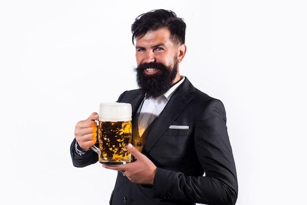 Bell'uomo in abito nero che beve birra su sfondo bianco.