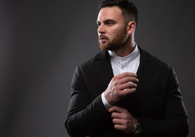 Un bell'uomo in abito nero e camicia bianca. un uomo d'affari in piedi su uno sfondo nero. foto del primo piano