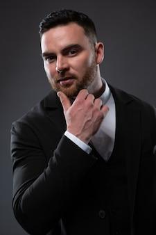 Un bell'uomo in abito nero e camicia bianca. un uomo d'affari in piedi su uno sfondo nero.
