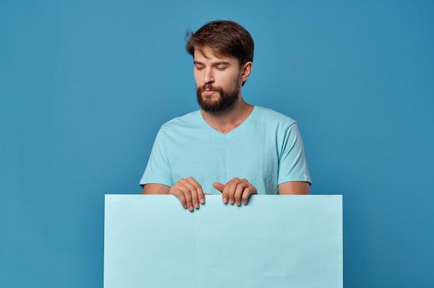 Uomo bello carta blu nelle mani di marketing divertente stile di vita sfondo blu